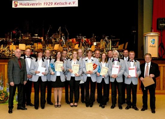 Eingebettet in das gelungene Konzert waren zahlreiche Ehrungen für langjährige und verdiente Mitglieder des Musikvereins. Vorsitzender Helmut Schäfer (rechts außen) bekam die Ehrennadel der Gemeinde Ketsch von Bürgermeister Jürgen Kappenstein (3. v. r.) verliehen.